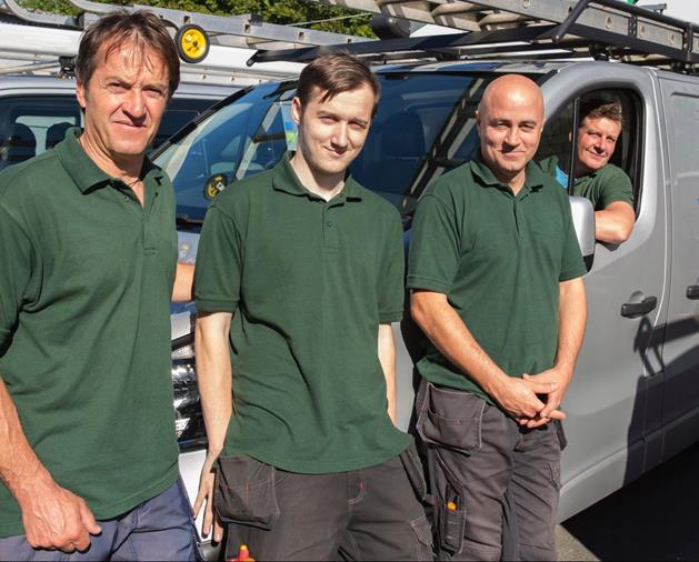 three men in green polos standing in front of ADA van with a fourth man in driver's seat