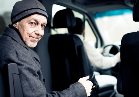 elderly man sitting in back of ADA vehicle being driven by second man